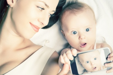 Image of funny baby and mother make selfie photo on mobile phone. Newborn looking at the camera surprised! Mothercare is most important in baby life