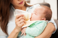 Closeup of a cute newborn baby drinking milk from a bottle while her mom hold her